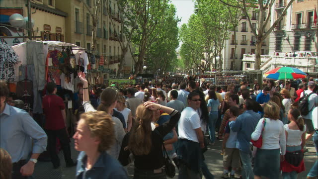 ws pan crowds in el rastro flea market, madrid, spain - mercato delle pulci video stock e b–roll