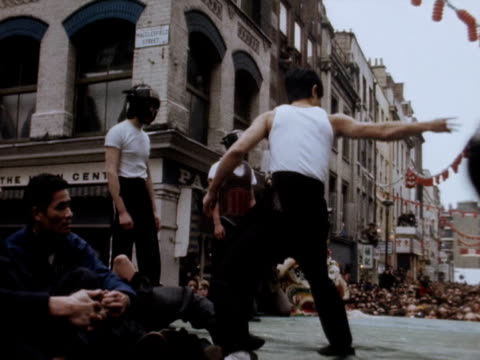 crowds in london's chinatown watch a kungfu display as part of the chinese new year celebrations - カンフー点の映像素材/bロール