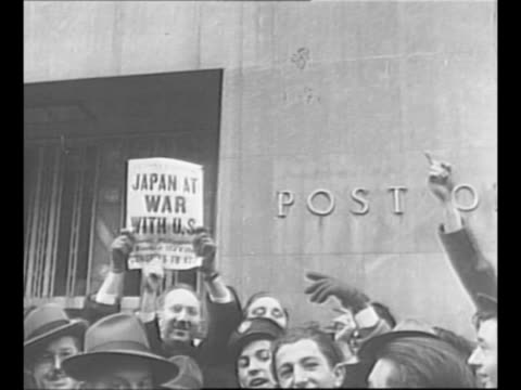 crowds in new york city / men gather around car listen to radio broadcast of us president franklin roosevelt's speech the day after the bombing of... - 真珠湾攻撃点の映像素材/bロール