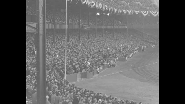 crowds in stands at baseball game at yankee stadium / cu new york yankees player lou gehrig smiles / another cu of gehrig he wears rain slicker - 1937 stock-videos und b-roll-filmmaterial