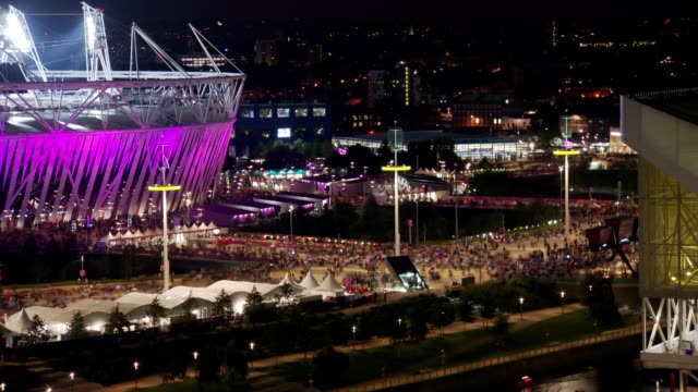 Crowds leave the London 2012 Olympic Stadium after the Men's 100m Final The stadium is lit up various colours from the lights around Timelapse...