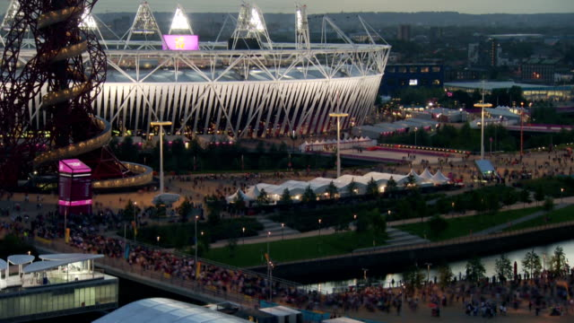 Crowds leave the park over the bridge and infront of the London 2012 Olympic Stadium which lights up as the sun goes down Timelapse Olympic Park...