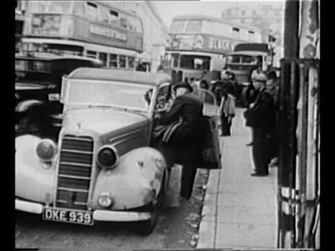 vídeos y material grabado en eventos de stock de crowds line london street as people run past as daily life continues during world war ii / man gets into parked car on street as double-decker buses... - el blitz
