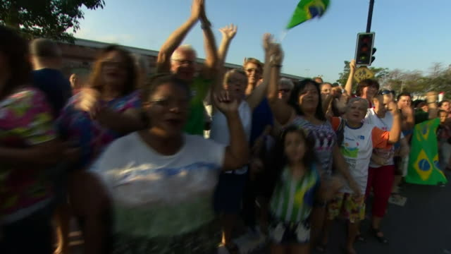 crowds lining the streets of rio de janeiro as they wait for the olympic torch relay to pass through - オリンピック大会点の映像素材/bロール