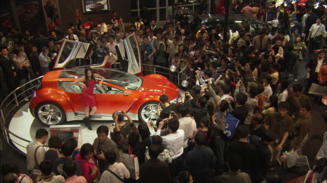 ws ha crowds looking at sports car at beijing auto show, beijing, china - 展覧会点の映像素材/bロール