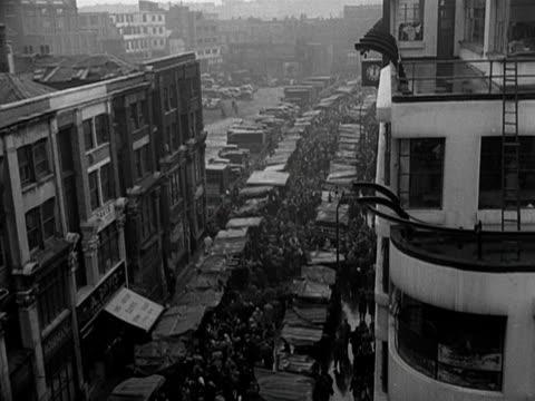 crowds move through petticoat lane market - mercato all'aperto video stock e b–roll
