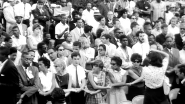 vídeos de stock e filmes b-roll de crowds of black and white people joining hands and singing the protest song we shall overcome after mlk delivered his i have a dream speech during... - 1963
