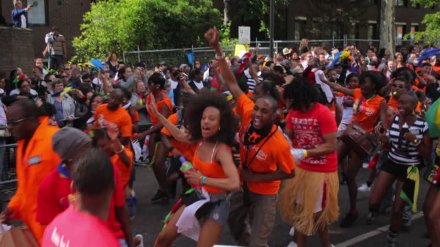 ws pan crowds of carnival goers dancing in notting hill carnival / london, united kingdom - parade stock videos & royalty-free footage