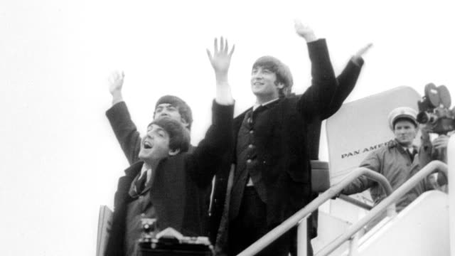 vídeos de stock e filmes b-roll de crowds of fans waiting at heathrow airport for the beatles to arrive / fans on rooftops with signs screaming and waving / cu teenage girl screaming... - the beatles
