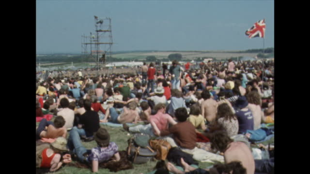 crowds of festival goers sitting and waiting in the sun; 1970 - sunbathing stock videos & royalty-free footage