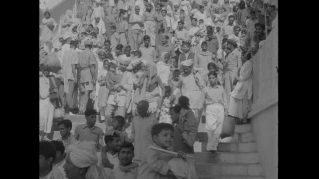 vidéos et rushes de crowds of indians walking, soldiers on the sidelines of crowds / throngs of people, mostly men, walk down stairs, some wear turbans / medium shot of... - fête religieuse