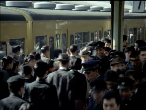 crowds of japanese commuters on subway platform / train entering station / people pushing and crowding onto subway. japanese commuters flooding into... - pushing stock videos & royalty-free footage