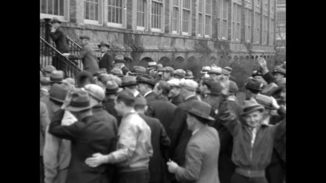 vs crowds of men walk some smoke some carry small parcels or lunch pails woman turns around as crowd of men walks away men wave hats as they enter... - machine valve stock videos & royalty-free footage