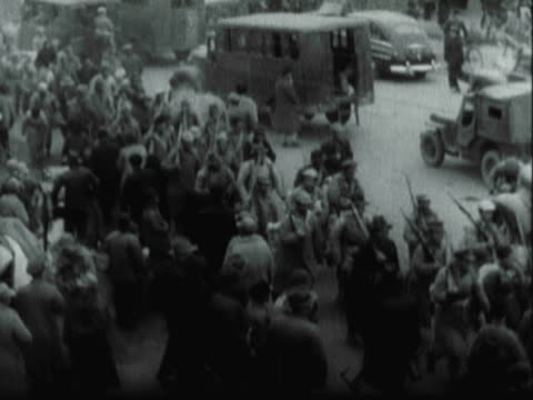 vídeos de stock, filmes e b-roll de montage crowds of north korean refugees fleeing through the streets carrying their bundles / north korea - 1951