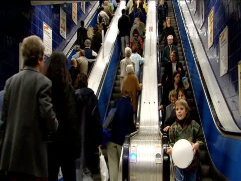 Crowds of passengers using U-Bahn underground escalators Munich