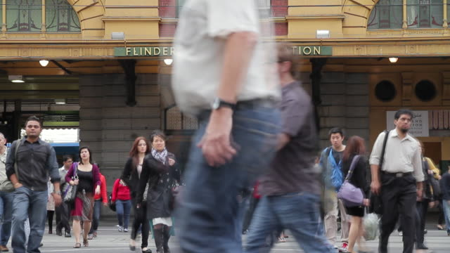 MS T/L Crowds of pedestrians cross busy city street as traffic stops at flinders street station / Melbourne, Victoria, Australia