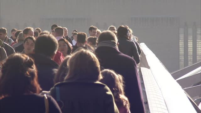 Crowds of pedestrians cross the Millennium bridge in London England. Available in HD.