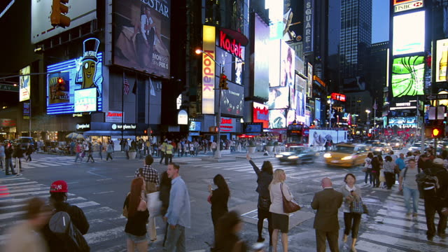 t/l crowds of pedestrians crossing street of busy city intersection / new york city, new york, united states - 電飾点の映像素材/bロール