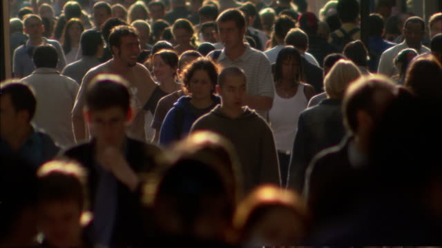 crowds of pedestrians walk on a busy sidewalk. - population explosion video stock e b–roll