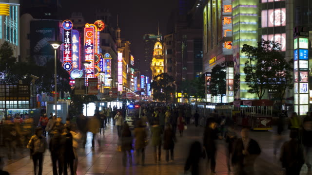 crowds of pedestrians walk pass stores along nanjing road in shanghai. - nanjing road stock videos & royalty-free footage