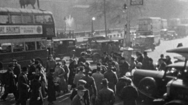 1937 montage crowds of pedestrians walking the sidewalks, passing between stopped traffic, crossing streets, running into charing cross station, and hopping onto moving buses / london, england, united kingdom - 1930 video stock e b–roll