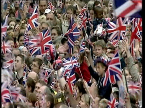 Crowds of people and children singing and waving Union flags outside Buckingham Palace celebrating Golden Jubilee London 04 Jun 02