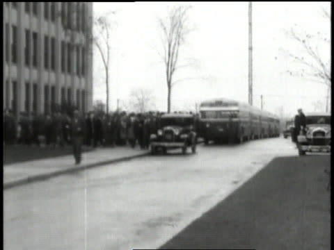 1932 MONTAGE Crowds of people and tour buses outside auto plant buildings / Michigan, United States