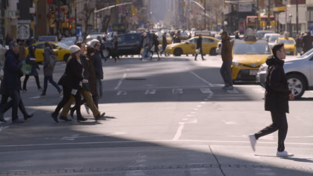 crowds of people cross a busy manhattan street on a cold winter/spring day. - fußgängerübergang stock-videos und b-roll-filmmaterial