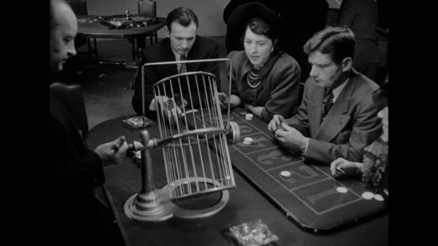 stockvideo's en b-roll-footage met 1948 crowds of people enjoy the games inside a bustling casino - casino