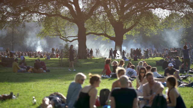 crowds of people gather at the london fields public park in spring. hackney, london,  uk. - park stock videos & royalty-free footage