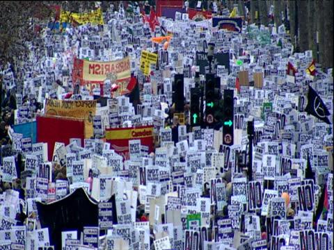 vídeos de stock e filmes b-roll de crowds of people holding placards surrounding traffic lights at antiwar demonstration 15 feb 03 - rodear