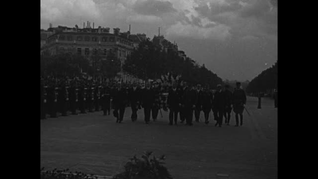 VS crowds of people in Paris street mostly men one man wearing a bunch of war medals holds back several other men / Polish Ambassador to France's...