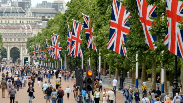 crowds of people in the mall london with union jack flags - bandiera del regno unito video stock e b–roll