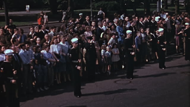 Crowds of people lining the road as President Franklin D Roosevelt's funeral procession travels down Pennsylvania Avenue / Washington DC United States