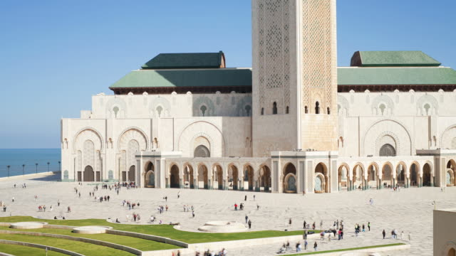 crowds of people move through the plaza outside the hassan ii mosque. - casablanca morocco stock videos & royalty-free footage