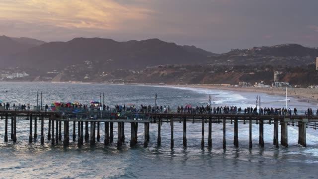 crowds of people on santa monica pier at dusk - aerial - santa monica sunset stock videos & royalty-free footage