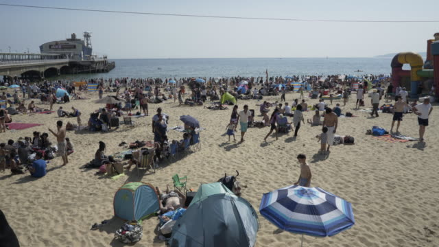 crowds of people on the beach. - beach umbrella stock videos and b-roll footage