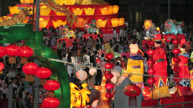 Crowds of people pass under colorful decorations in celebration of the Chinese New Year.