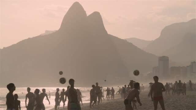 ls crowds of people play football on ipanema beach at sunset / rio de janeiro - swimming shorts stock videos & royalty-free footage