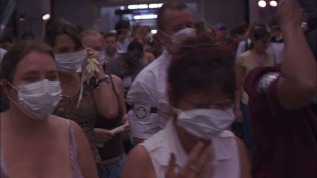 vídeos de stock, filmes e b-roll de crowds of people put on surgical masks while they move forward. - máscara cirúrgica