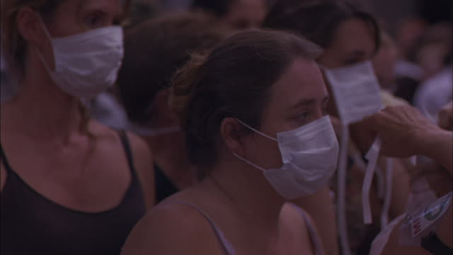 crowds of people put on surgical masks while they move forward. - mundschutz stock-videos und b-roll-filmmaterial