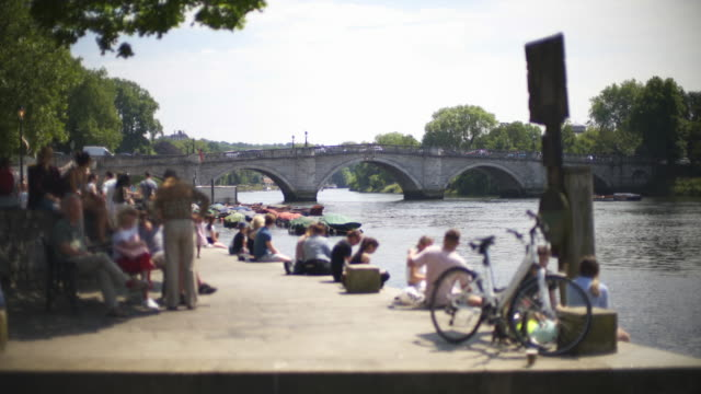 crowds of people relaxing on a summers afternoon on the banks of the river thames close to richmond bridge. - richmond upon thames stock-videos und b-roll-filmmaterial