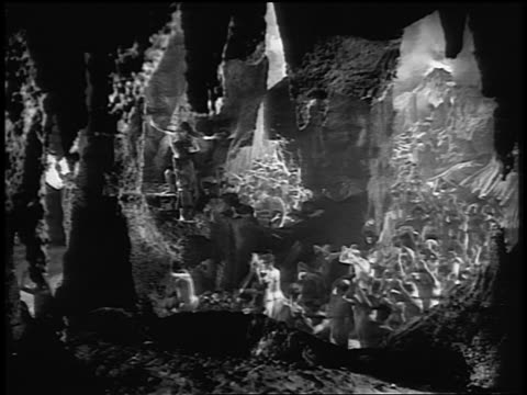 B/W crowds of people running back + forth + writhing in caves of Hell / Legend of Faust