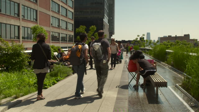 Crowds of people walk and relax on top of the Highline park in New York city.
