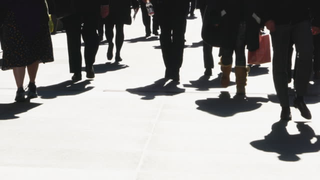 crowds of people walk down the sidewalk, which are illuminated by strong sunlight and reflect the shadows on the ground at midtown manhattan ny usa on nov. 08 2018. - lunch stock videos & royalty-free footage