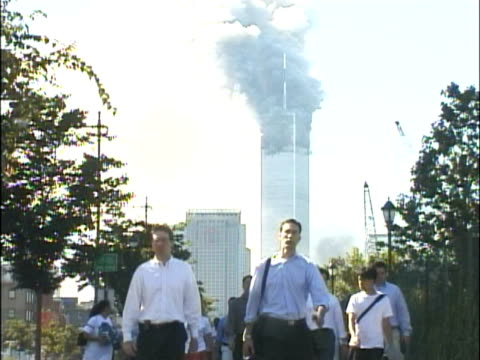 Crowds of people walking along the West Side Highway away from the burning World Trade Center The South Tower 2 has already collapsed Smoke pouring...