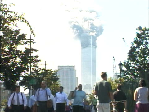 crowds of people walking along the west side highway away from the burning world trade center building smoke pouring from the north tower 1 various... - terrorism stock videos & royalty-free footage