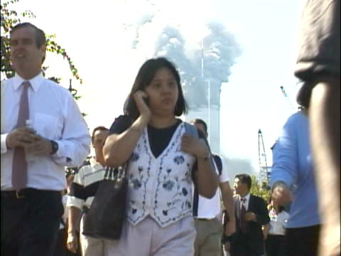 vidéos et rushes de crowds of people walking along the west side highway away from the burning world trade center building smoke pouring from the north tower 1 various... - attentat du 11 septembre 2001