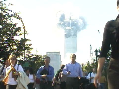 crowds of people walking along the west side highway, away from the burning world trade center building. smoke pouring from the north tower 1.... - terroranschläge vom 11. september 2001 stock-videos und b-roll-filmmaterial