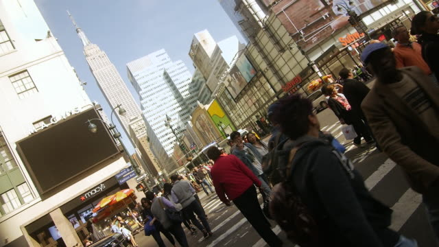Crowds of people walking and crossing street in rush hour in New York City with Empire state building in the background